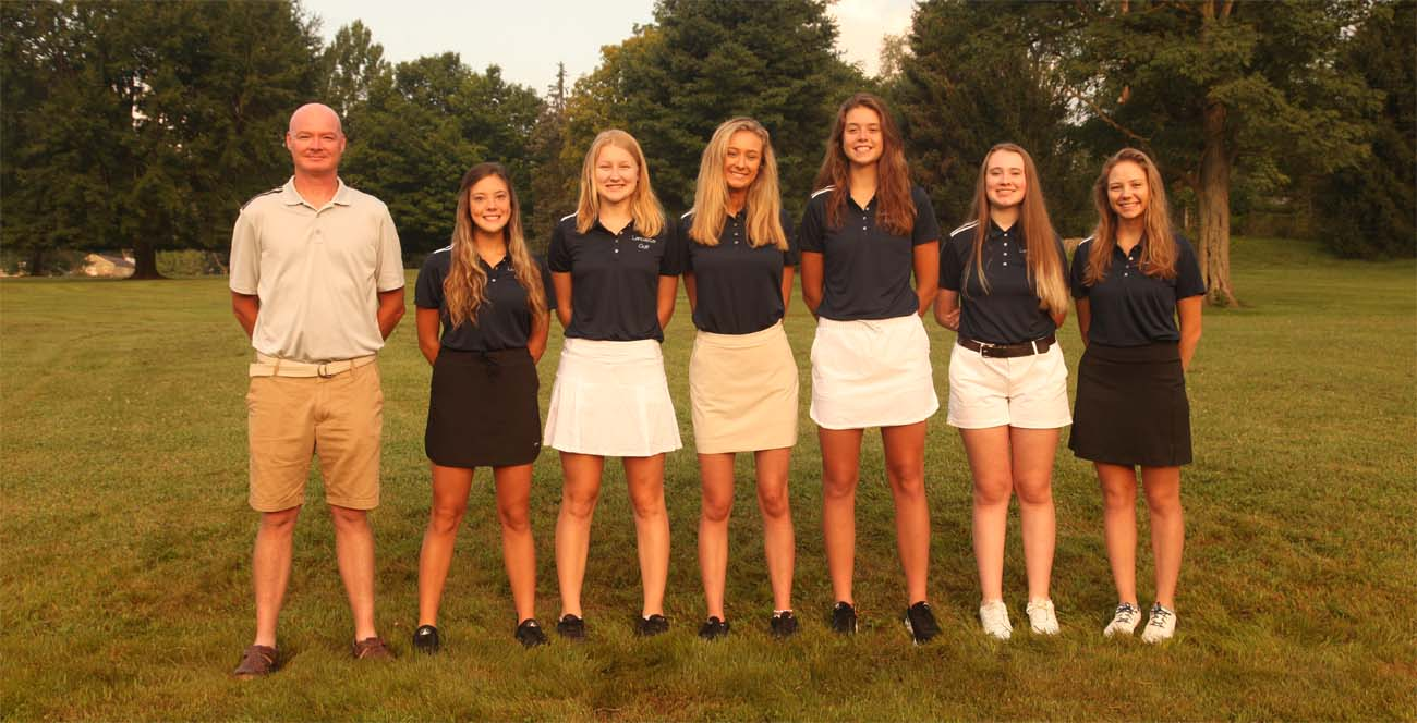 girls standing with coach outside for golf team photo